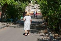 Mujer mayor en sombrero y con un bastón que camina abajo de la calle Imágenes de archivo libres de regalías