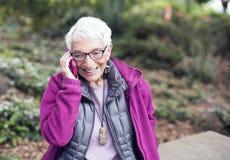 Mujer mayor en sus años ochenta en el teléfono móvil en parque Foto de archivo
