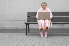 Mujer mayor en traje rosado al aire libre con la computadora portátil Imagen de archivo libre de regalías