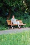 Mujer mayor en un pensamiento del banco de parque Imagen de archivo libre de regalías