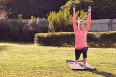 Mujer mayor en una actitud del guerrero de la yoga en hierba Fotografía de archivo libre de regalías