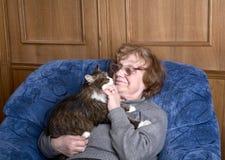 Mujer mayor en una butaca con un gato Imágenes de archivo libres de regalías