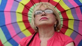 Mujer mayor en vidrios con el paraguas colorido metrajes