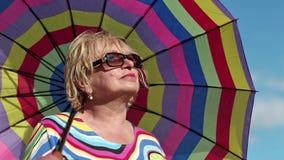 Mujer mayor en vidrios con el paraguas colorido almacen de video