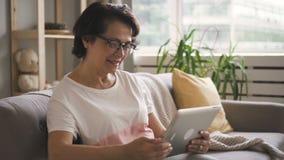 Mujer mayor en vidrios que sonríe disfrutando de la llamada video almacen de video