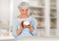 Mujer mayor encantadora que aplica la crema cosmética en su cara para el cuidado de piel facial en cuarto de baño en casa Foto de archivo libre de regalías