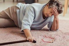 Mujer mayor enferma con dolor de cabeza fotos de archivo