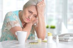 Mujer mayor enferma con la medicación Imagenes de archivo