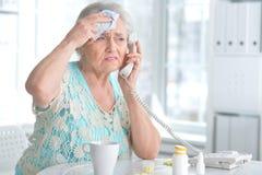 Mujer mayor enferma con la medicación Foto de archivo libre de regalías