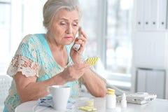Mujer mayor enferma con la medicación Fotos de archivo