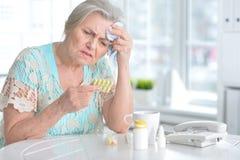 Mujer mayor enferma con la medicación Imágenes de archivo libres de regalías