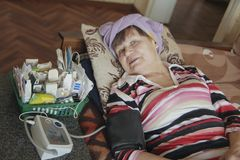 Mujer mayor enferma que miente en la cama con las tabletas y el dispositivo para medir la presión imágenes de archivo libres de regalías