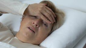 Mujer mayor enferma que toca la frente con la mano de temblor, fiebre durante la gripe, virus almacen de metraje de vídeo