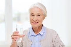 Mujer mayor feliz con el vidrio de agua en casa Imagenes de archivo
