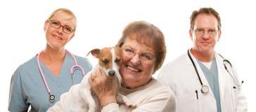Mujer mayor feliz con las personas del perro y del veterinario Imagenes de archivo
