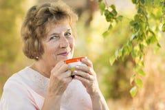 Mujer mayor feliz con una taza de bebida Foto de archivo libre de regalías