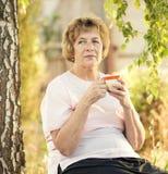 Mujer mayor feliz con una taza de bebida Foto de archivo