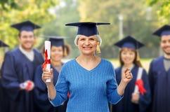 Mujer mayor feliz del estudiante de tercer ciclo con el diploma imagen de archivo libre de regalías
