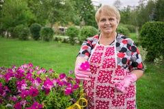 Mujer mayor feliz en el jardín que muestra las flores coloridas Fotos de archivo