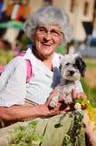 Mujer mayor feliz en la montaña con el ramo de flores del bosque y de su perro Imagen de archivo