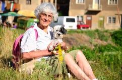 Mujer mayor feliz en la montaña con el ramo de flores del bosque y de su perro Imágenes de archivo libres de regalías