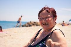 Mujer mayor feliz en la playa Imágenes de archivo libres de regalías
