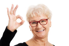Mujer mayor feliz en los vidrios del ojo que muestran MUY BIEN. foto de archivo libre de regalías