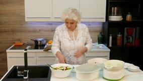 Mujer mayor feliz que cocina la cena para la familia grande almacen de video