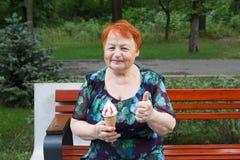 Mujer mayor feliz que come el helado foto de archivo