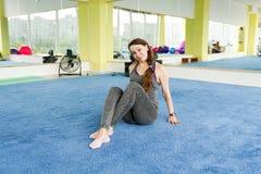 Mujer mayor feliz que descansa sobre la estera después de ejercicio en gimnasio fotos de archivo