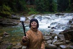 Mujer mayor feliz que goza cerca de una corriente de la montaña Imágenes de archivo libres de regalías