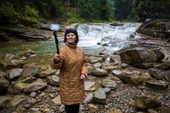 Mujer mayor feliz que goza cerca de una corriente de la montaña Imagen de archivo