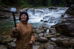Mujer mayor feliz que goza cerca de una corriente de la montaña Imagen de archivo libre de regalías