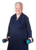 Mujer mayor feliz que hace el entrenamiento de la aptitud con pesas de gimnasia Fotografía de archivo libre de regalías