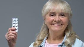Mujer mayor feliz que muestra el arenador de las píldoras, atención sanitaria, tratamiento de la enfermedad, vitaminas almacen de video