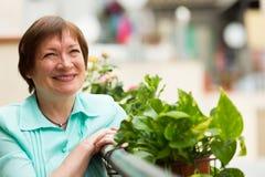 Mujer mayor feliz que se sienta en balcón imagen de archivo libre de regalías