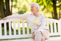 Mujer mayor feliz que se sienta en banco en el parque del verano foto de archivo