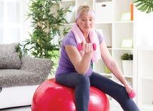 Mujer mayor feliz que se sienta en bola del gimnasio, y ejercicio con el dumbbe Imagen de archivo