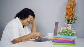 Mujer mayor feliz que trabaja en el ordenador portátil almacen de metraje de vídeo