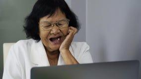 Mujer mayor feliz que trabaja en el ordenador portátil metrajes