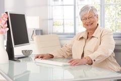 Mujer mayor feliz que usa el ordenador en casa Imagen de archivo