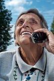 Mujer mayor feliz que usa el teléfono sin cuerda Foto de archivo
