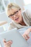 Mujer mayor feliz que usa la tableta fotos de archivo