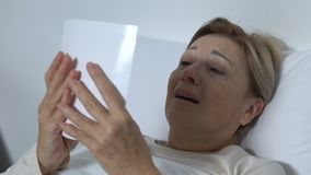 Mujer mayor gritadora que miente en cama y que mira la foto, recordando al marido metrajes