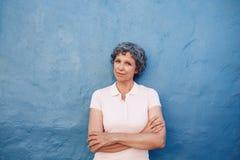 Mujer mayor hermosa que se coloca con sus brazos cruzados Imagen de archivo libre de regalías