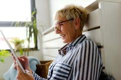 Mujer mayor hermosa sonriente que usa la tableta digital en casa imagen de archivo libre de regalías