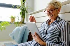 Mujer mayor hermosa sonriente que usa la tableta digital en casa fotos de archivo