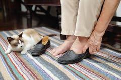 Mujer mayor hinchada pies que ponen en los zapatos imagen de archivo