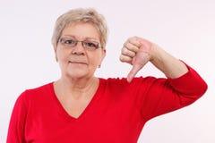 Mujer mayor infeliz que muestra los pulgares abajo, emociones negativas en edad avanzada Fotos de archivo