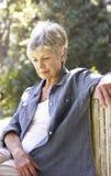 Mujer mayor infeliz que se sienta en banco de parque Fotos de archivo